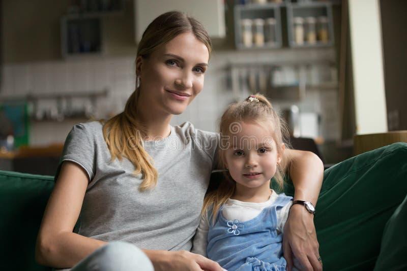 Retrato de la niña de abarcamiento cariñosa de la madre soltera en el sofá fotos de archivo