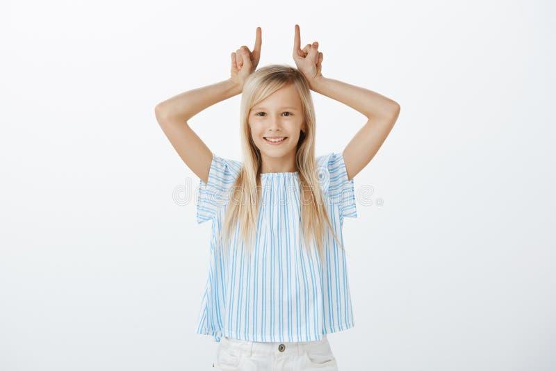 Retrato de la niña adorable juguetona con el pelo rubio, divirtiéndose mientras que imita en los padres, siendo obstinado, sosten imágenes de archivo libres de regalías