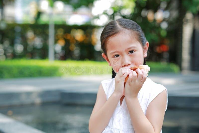 Retrato de la niña asiática que come el pan con el postre Fresa-llenado relleno y manchado alrededor de su boca en jardín al aire fotos de archivo