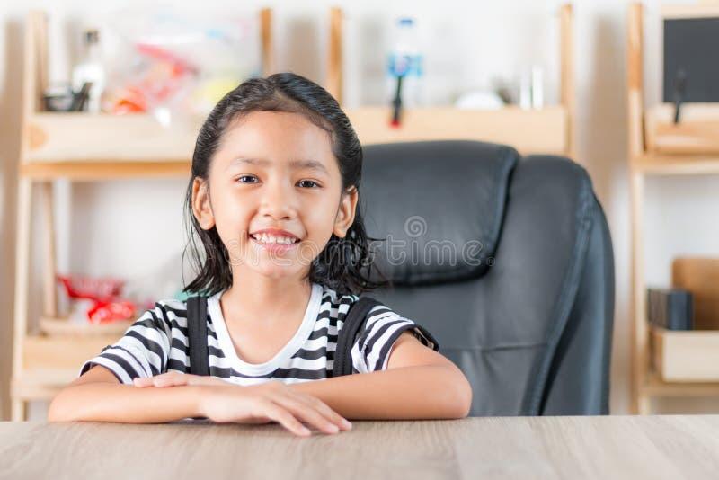 Retrato de la niña asiática que se sienta en la tabla de madera fotografía de archivo libre de regalías