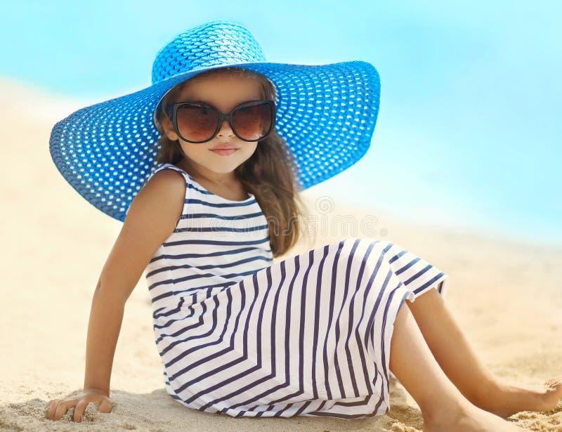 Retrato de la niña bonita en una reclinación de relajación rayada del sombrero del vestido y de paja sobre la playa cerca del mar fotos de archivo libres de regalías