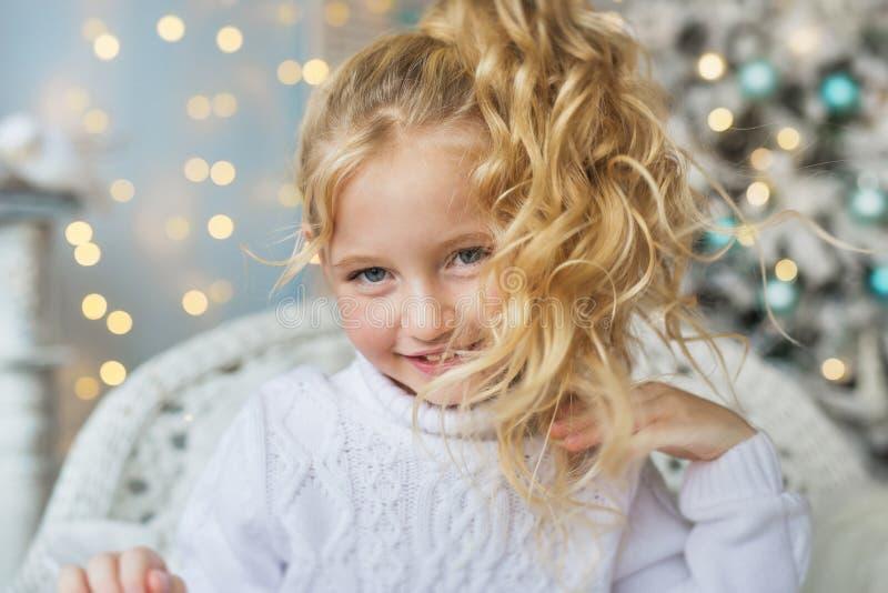 Retrato de la niña bonita rubia en el suéter blanco en una silla en la Navidad imágenes de archivo libres de regalías