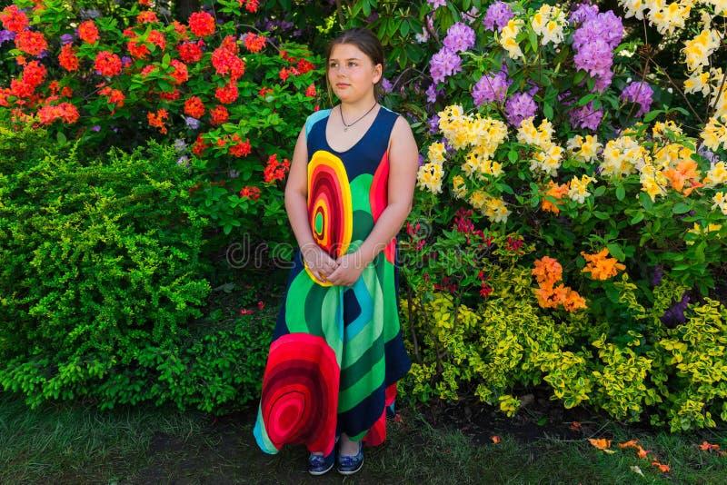 retrato de la niña de moda elegante que se coloca en jardín botánico fotos de archivo libres de regalías