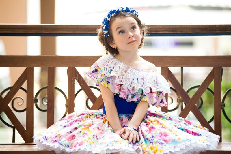 Retrato de la niña de moda que se sienta en un banco fotografía de archivo