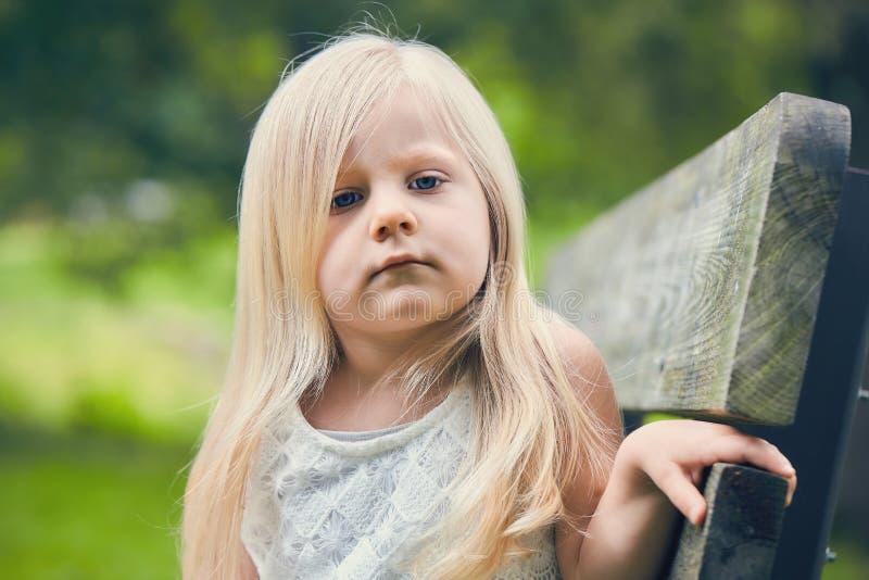 Retrato de la niña descontentada que se sienta en banco imágenes de archivo libres de regalías