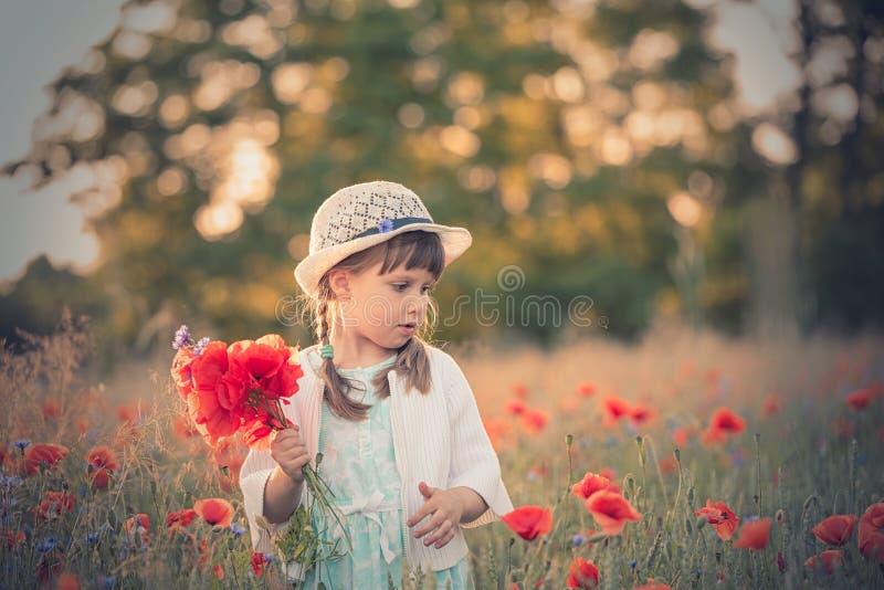 Retrato de la niña en el campo de la amapola del redd foto de archivo