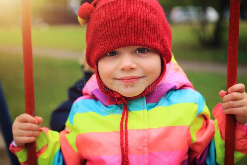 Retrato de la niña en el oscilación Niños que montan en el carrusel Cabritos en patio foto de archivo