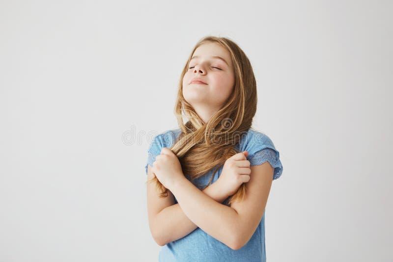 Retrato de la niña encantadora con el pelo ligero en la presentación divertida de la camiseta azul para la imagen con los ojos ce imágenes de archivo libres de regalías