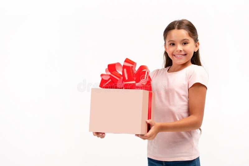 Retrato de la niña feliz con el rectángulo de regalo sobre el fondo blanco imagen de archivo