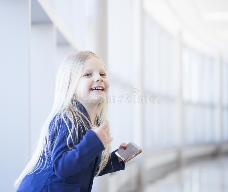 Retrato de la niña feliz con el smartphone que mira la cámara imágenes de archivo libres de regalías