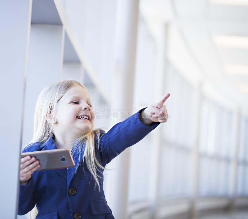 Retrato de la niña feliz con el smartphone que muestra algo imagenes de archivo