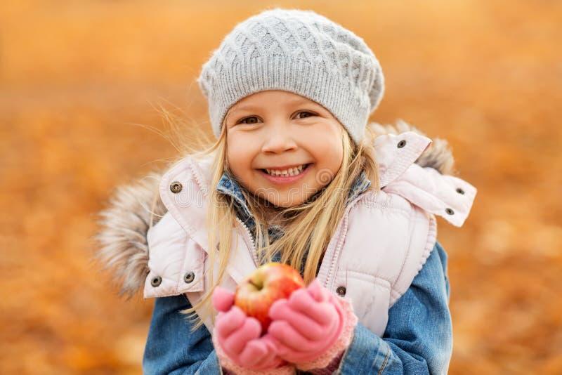 Retrato de la niña feliz con la manzana en otoño imagen de archivo libre de regalías