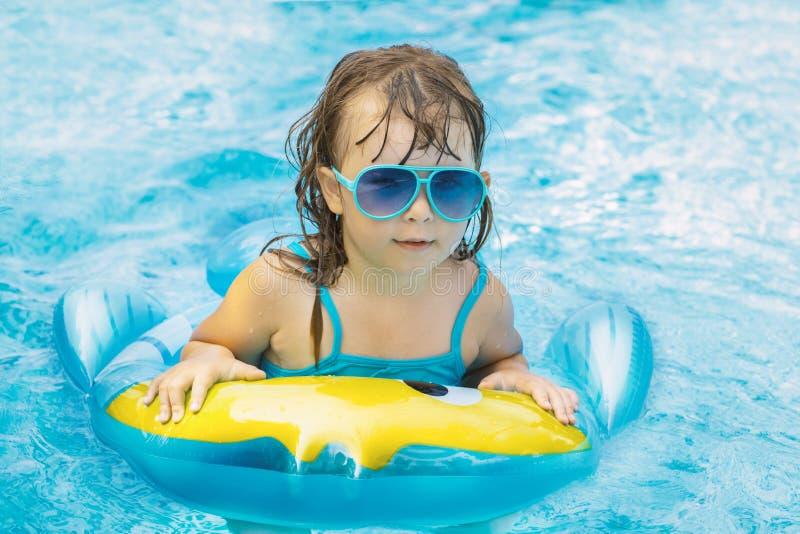 Retrato de la niña feliz linda que se divierte en piscina, flotando en anillo de goma de restauración azul del ingenio del agua,  imagenes de archivo
