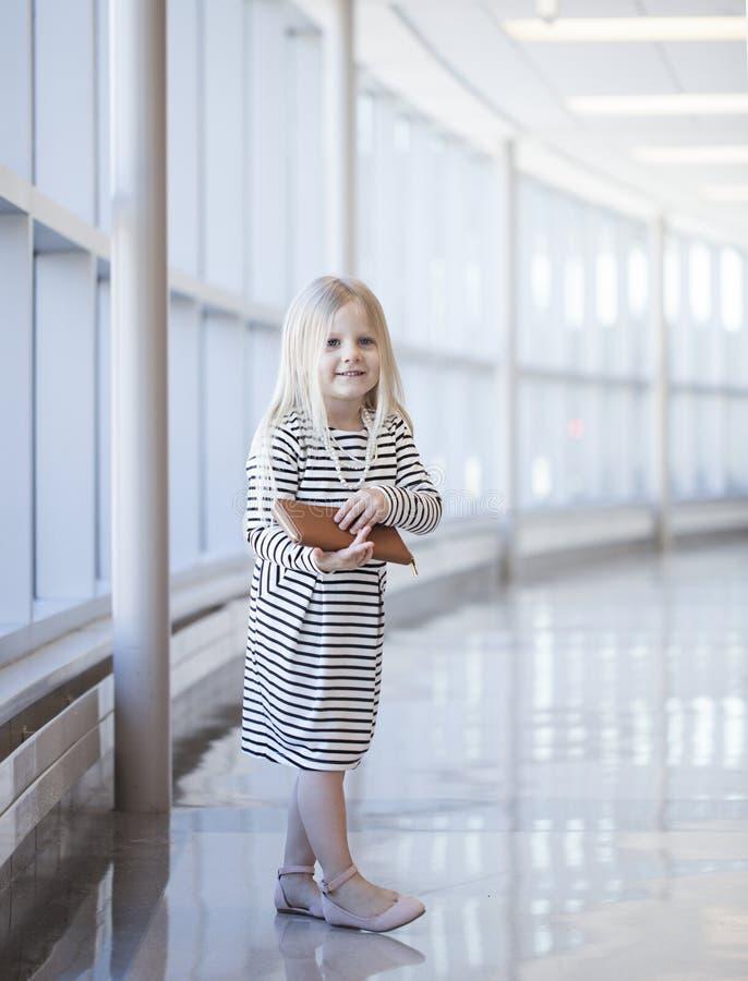 Retrato de la niña feliz que lleva el vestido rayado con la cartera fotos de archivo libres de regalías
