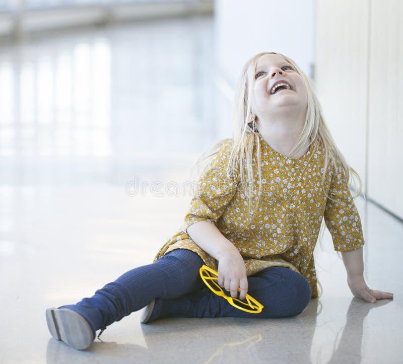 Retrato de la niña feliz que se sienta en la pared y la risa imagenes de archivo
