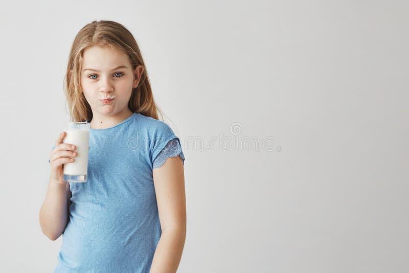 Retrato de la niña linda con el pelo largo rubio y los ojos azules que miran in camera con el bigote de la leche y la cara divert imagen de archivo libre de regalías