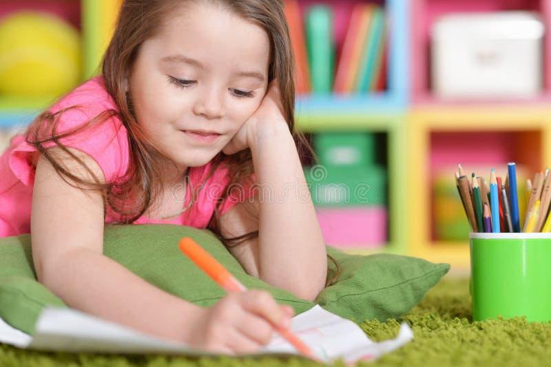 Retrato de la niña linda en el dibujo rosado de la camisa foto de archivo libre de regalías