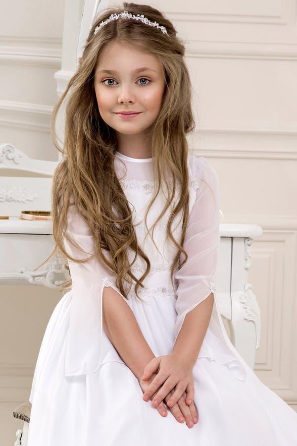 Retrato de la niña linda en el vestido y la guirnalda blancos en la primera puerta de la iglesia del fondo de la comunión santa foto de archivo libre de regalías