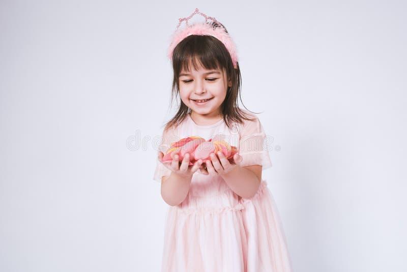Retrato de la niña linda que lleva el vestido rosado en Tulle con la corona de la princesa en la cabeza en el fondo blanco antes  imagen de archivo libre de regalías