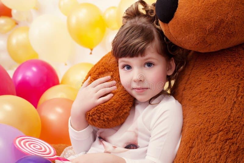 Retrato de la niña preciosa que abraza el oso de peluche imagen de archivo