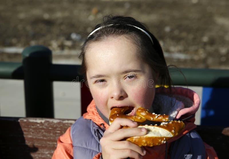 Retrato de la niña que come el pretzel fotos de archivo libres de regalías