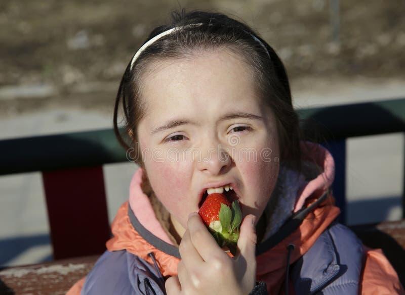Retrato de la niña que come la fresa imagen de archivo