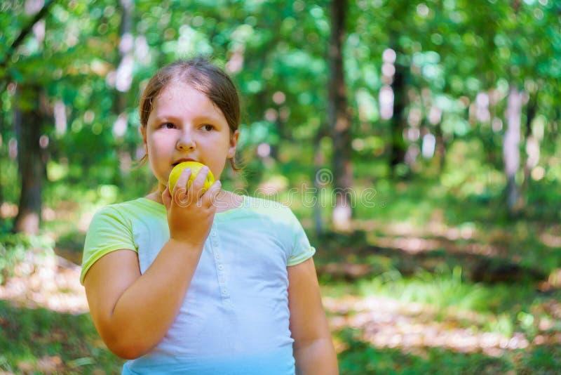 Retrato de la niña que come la manzana al aire libre de la manzana al día de verano imagenes de archivo