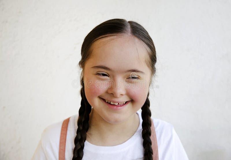 Retrato de la niña que sonríe en el fondo de la pared imagen de archivo libre de regalías