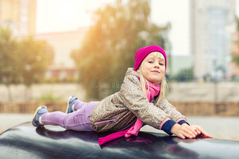 Retrato de la niña rubia caucásica linda que se divierte que juega en el patio al aire libre moderno en el parque de la ciudad en fotografía de archivo