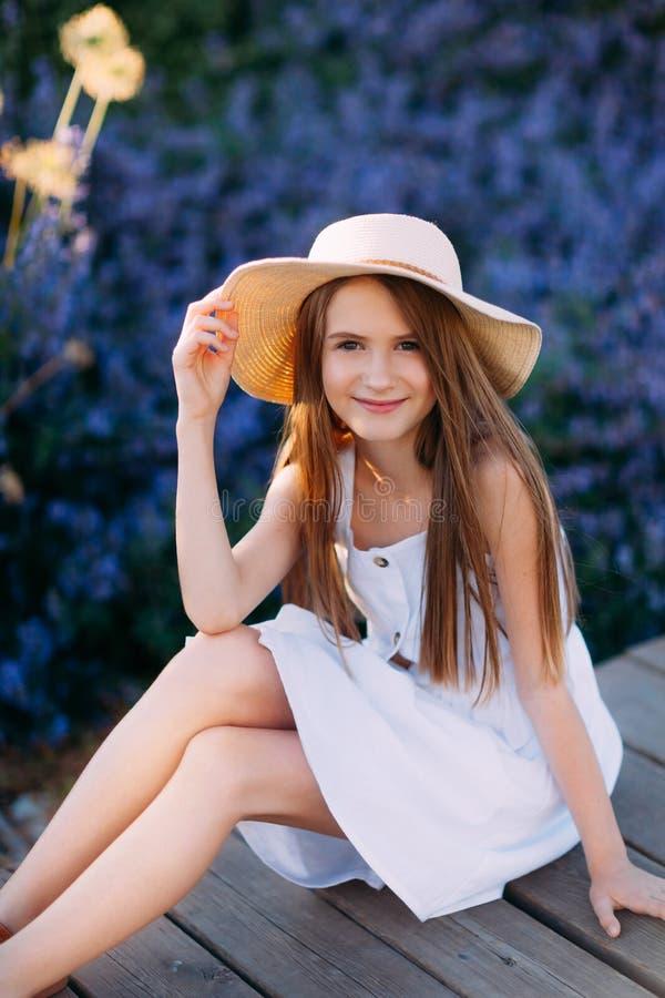 Retrato de la niña sonriente en el vestido y el sombrero blancos foto de archivo libre de regalías