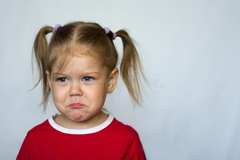 Retrato de la niña triste con los ojos azules que miran a un lado en el fondo blanco fotos de archivo libres de regalías