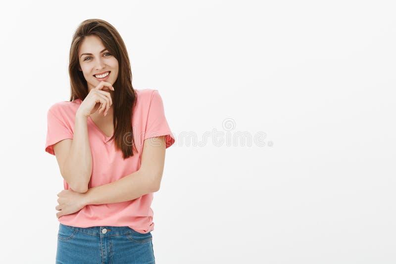 Retrato de la novia apuesta en camiseta rosada y de los vaqueros, riendo, llevando a cabo la mano en la barbilla y sonriendo ampl foto de archivo libre de regalías