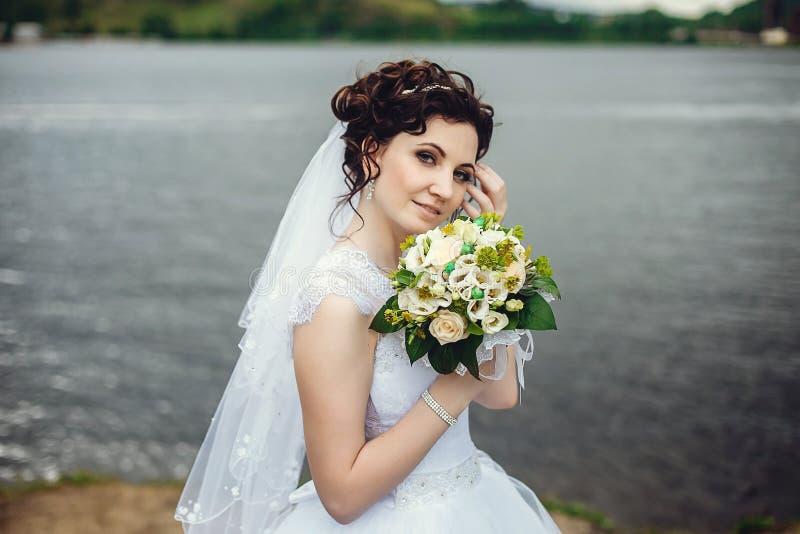 Retrato de la novia en un vestido blanco en naturaleza Novia elegante que sostiene su ramo de la boda foto de archivo libre de regalías