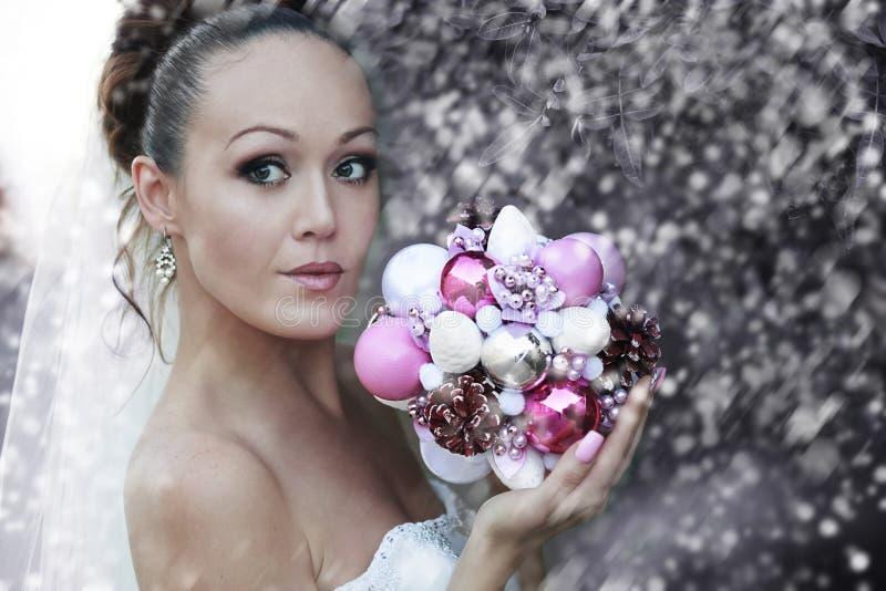 Retrato de la novia en velar nupcial blanco con la sesión de foto artificial del manojo, las hojas y el fondo de los árboles, art fotografía de archivo