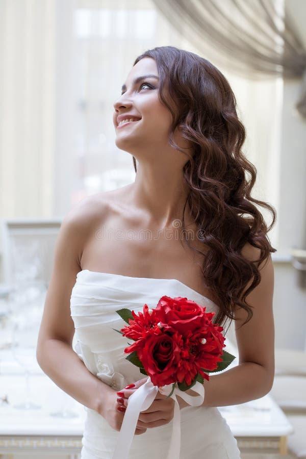 Retrato de la novia feliz que presenta con el ramo rojo fotografía de archivo