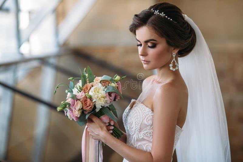 Retrato de la novia hermosa con las flores del ramo en el vestido de lujo blanco Modelo magnífico con maquillaje y el peinado nup imagen de archivo