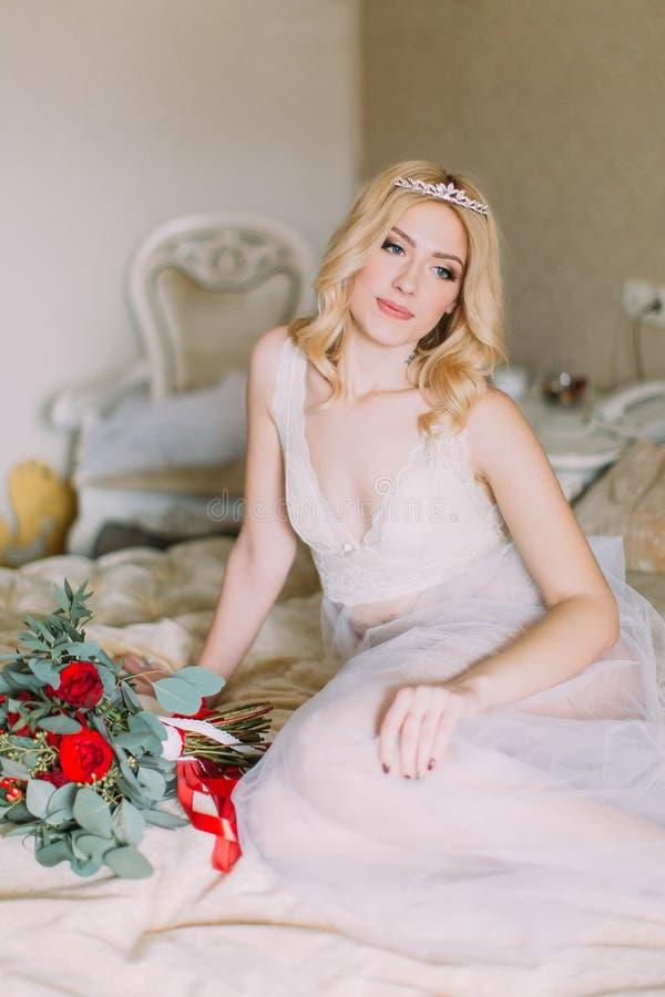 Retrato de la novia rubia atractiva en la ropa interior blanca que se sienta en cama Ramo con las rosas rojas imagenes de archivo