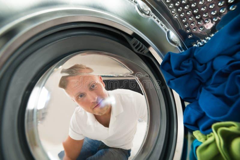 Retrato de la opinión del hombre por dentro de la lavadora imágenes de archivo libres de regalías