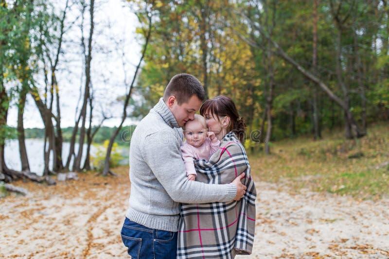 Retrato de la pareja feliz que abraza a su pequeña hija sobre un fondo del bosque foto de archivo