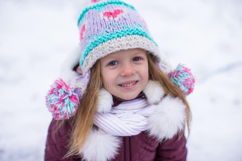 Retrato de la pequeña muchacha adorable en la nieve soleada imagen de archivo libre de regalías