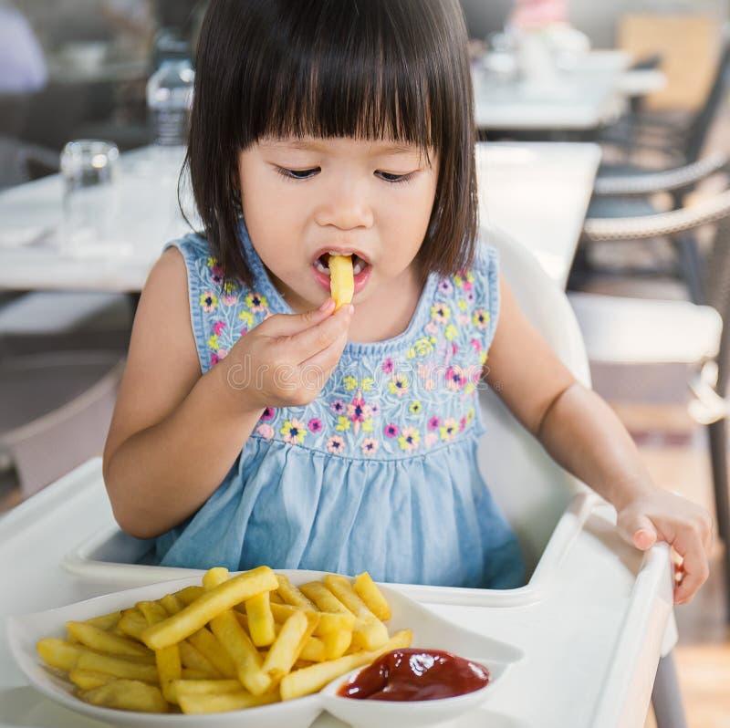 Retrato de la pequeña muchacha asiática en restaurante de los alimentos de preparación rápida fotos de archivo libres de regalías