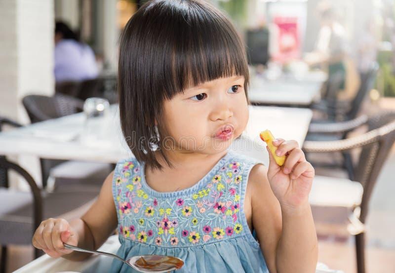 Retrato de la pequeña muchacha asiática en restaurante de los alimentos de preparación rápida fotografía de archivo libre de regalías