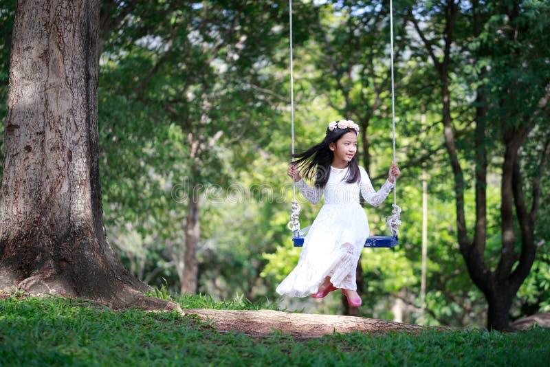 Retrato de la pequeña muchacha asiática que juega el oscilación debajo del árbol grande con la profundidad baja del foco selecto  foto de archivo libre de regalías