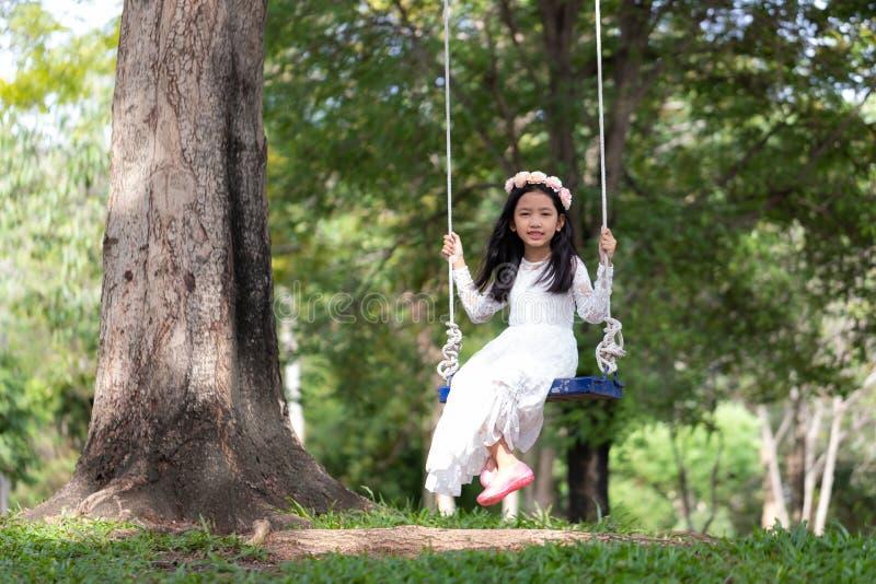 Retrato de la pequeña muchacha asiática que juega el oscilación debajo del árbol grande en el bosque de la naturaleza con tono su fotografía de archivo libre de regalías