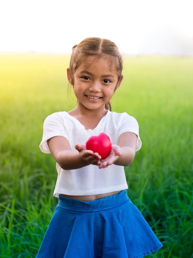 Retrato de la pequeña muchacha asiática que lleva a cabo el corazón rojo y smilling fotos de archivo