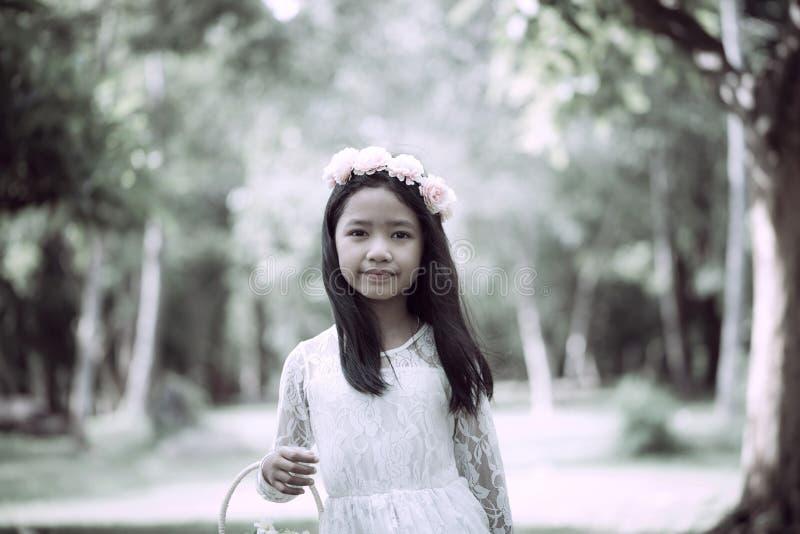 Retrato de la pequeña muchacha asiática que sonríe en el bosque de la naturaleza con tono de la suavidad y del vintage procesado imagen de archivo libre de regalías