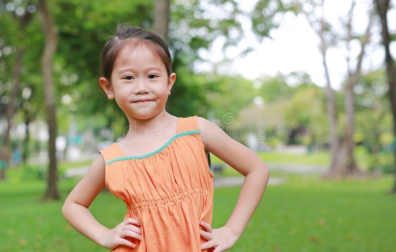 Retrato de la pequeña muchacha asiática sonriente del niño en parque de naturaleza con la mirada de la cámara fotos de archivo libres de regalías