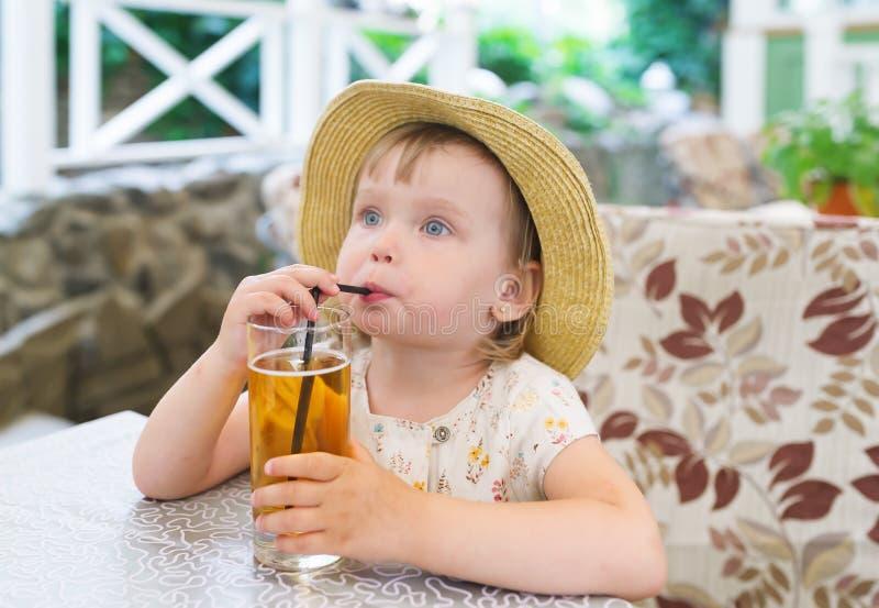 Retrato de la pequeña muchacha caucásica adorable linda en el sombrero de paja que se sienta en café que bebe té frío fotos de archivo