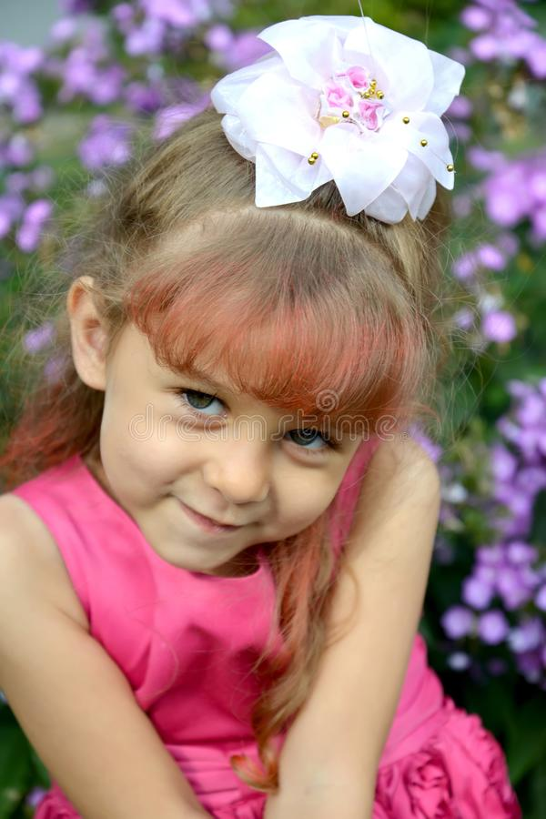 Retrato de la pequeña muchacha coqueta en un jardín imagen de archivo