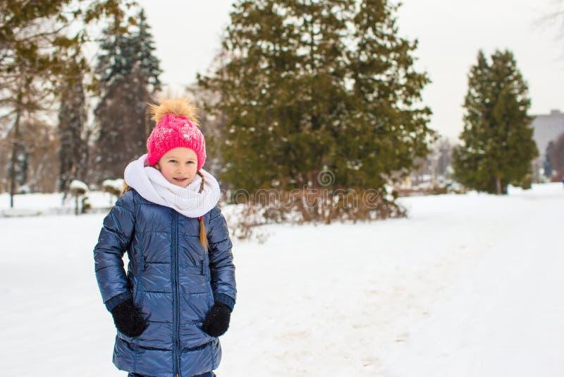 Retrato de la pequeña muchacha feliz en la nieve soleada fotos de archivo